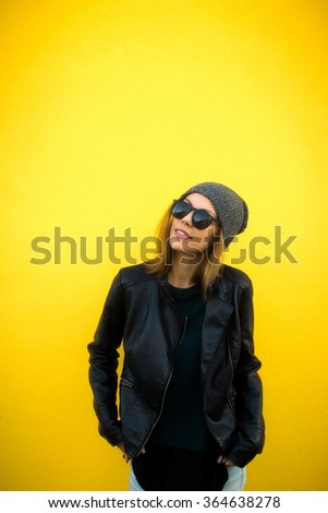 Trendy beautiful cool hipster blond girl wearing a gray hat, black leather jacket and glasses posing against a yellow wall. Street fashion concept, Urban style. - stock photo