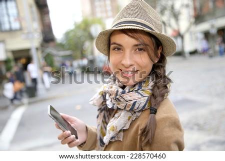 Trendy brunette girl in the street using smartphone - stock photo