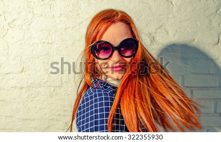 Trendy carrot-top girl turn around with her hair fly about her. Young woman weared in 60th fashion style sunglasses look back. A lot of copy space on white brick wall. - stock photo