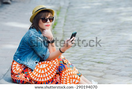 Trendy cool hipster woman colorful wearing sunglasses and hat. Sitting on the curb and looking at the mobile phone. Copy space. - stock photo