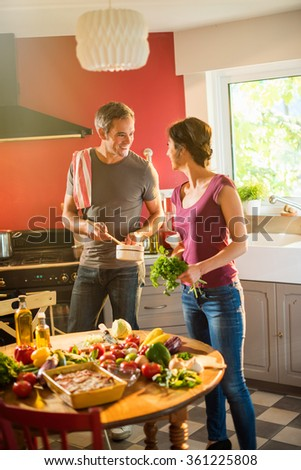 Trendy couple cooking vegetables from the market in a red kitchen. The grey hair man is steering the sauce in a white pan while the woman is taking care of the fresh vegetables.Backlit shot with flare