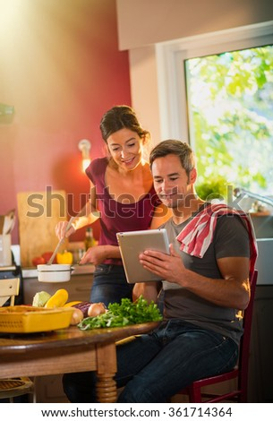 Trendy couple in casual clothes cooking vegetables from the market in a red kitchen. The woman is stirring the sauce in a white pan while the man is looking at recipes on tablet.shot with flare - stock photo