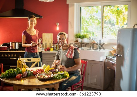 Trendy couple in casual clothes looking at camera while cooking vegetables from the market in a red kitchen. The woman is stirring ingredients in a pan while the grey hair man cut the fresh vegetables - stock photo
