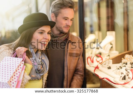 Trendy couple is looking for valentine'gifts. A grey hair man with beard and a woman with a black hat are standing in front of a jewelry shop. They are looking at the shop window. - stock photo