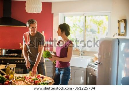 Trendy couple peeling and cutting vegetables from the market. They are smiling, wearing casual clothes, standing in front of the table in their red retro kitchen, cooking healthy food for the weekend - stock photo