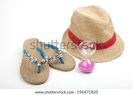 Trendy decorated blue beach shoes with rope soles and straw hat with an hourglass on a white background, conceptual of timing exposure to the sun while sunbathing at the coast - stock photo