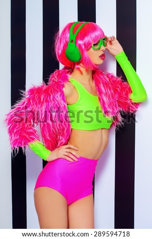 Trendy DJ girl in bright colorful clothes and headphones posing over black-and-white stripes. Party style. Fashion studio shot. - stock photo