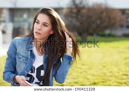 Trendy fashionable girl listening music by smartphone