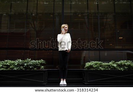 Trendy female hipster have smart phone conversation while standing outdoors in urban setting on black blank copy space background for your text,young business woman talking on her mobile phone in city - stock photo
