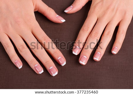 Trendy french manicure on a brown background.
