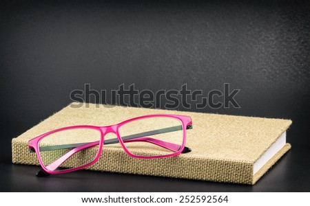 Trendy fuchsia pink glasses resting on a burlap covered book with black background. Photograph is cross processed with added grain and vignette.. - stock photo