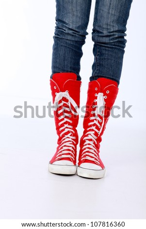 Trendy funky female or male hi top red canvas and white rubber boxing style trainer boots worn with blue jeans and both feet facing forwards