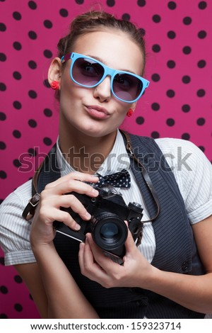 Trendy girl in glasses playing the ape with camera. Duckface. Pouting lips - stock photo