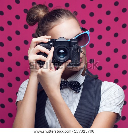 Trendy girl in sunglasses shooting with retro camera. Hipster style. Pink polka background - stock photo