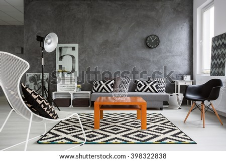 Trendy, grey living room with sofa, chairs, standing lamp, wood coffee-table and pattern decorations in black and white  - stock photo