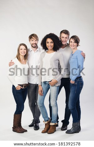 Trendy group of diverse young friends standing grouped around an attractive young African American woman on a grey studio background - stock photo