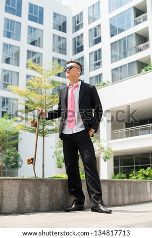 Trendy guy in business suit standing in urban environment holding a skateboard and listening to music
