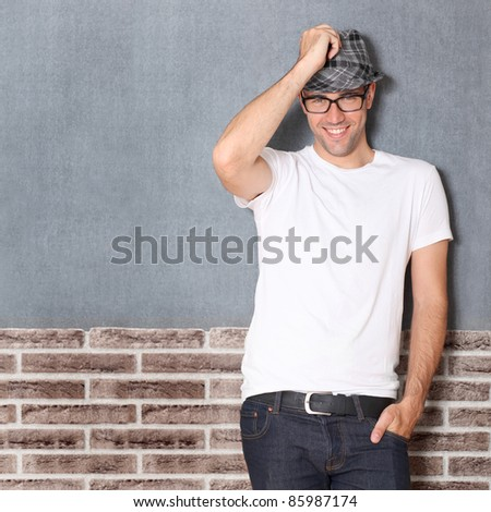 Trendy guy leaning on brick wall