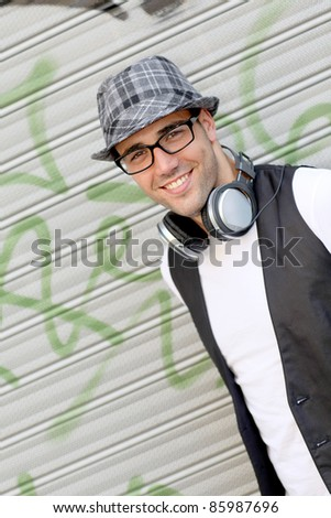 Trendy guy leaning on metal curtain in town - stock photo
