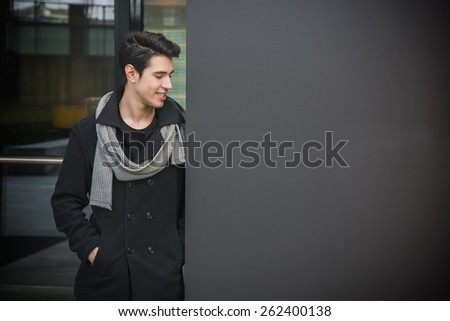 Trendy handsome young man in winter fashion standing against wall in urban environment looking at copyspace with a smile - stock photo