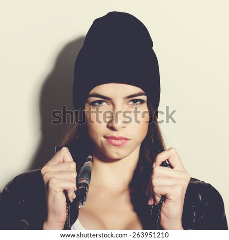 Trendy hipster Caucasian brunette teenage girl with black beanie hat and black leather jacket posing making facial expression. Medium retouch, square format, matte instagram look filter.