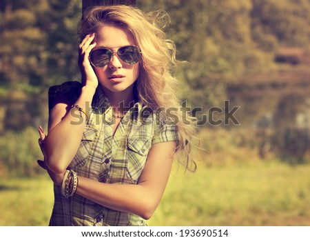 Trendy Hipster Girl in Sunglasses Touching Her Face. Summer Modern Youth Lifestyle. Toned Photo. - stock photo