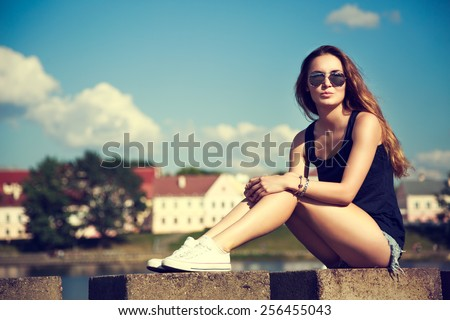 Trendy Hipster Girl Relaxing in the Park. Toned and Filtered Instagram Styled Photo. Modern Youth Lifestyle Concept.