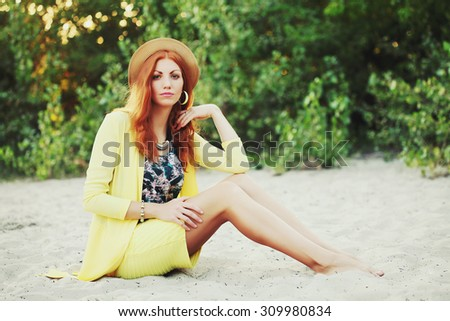 Trendy Hipster Girl Relaxing on the beach. Toned and Filtered Photo. Modern Youth Lifestyle Concept with a retro vintage instagram filter. - stock photo