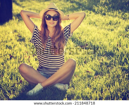 Trendy Hipster Girl Relaxing on the Grass. Toned and Filtered Photo. Modern Youth Lifestyle Concept.