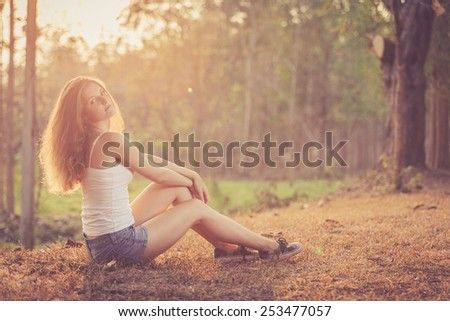 Trendy Hipster Girl Relaxing on the road near tree at the day time. Concept of Modern Youth Lifestyle.  Blowing Long Hair.  Glow Sun, Sunshine. Backlit. Toned in warm colors