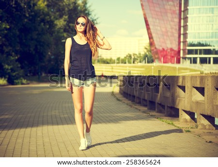 Trendy Hipster Girl Walking in the Park. Toned and Filtered Photo. Modern Youth Lifestyle Concept. - stock photo