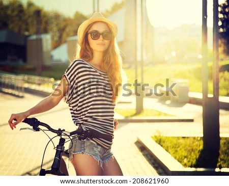 Trendy Hipster Girl with Bike on Urban Background. Toned and Filtered Photo. Modern Youth Lifestyle Concept. - stock photo
