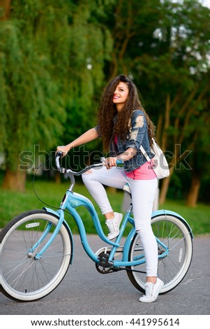Trendy Hipster Girl with curly hair and bike smiling at sunset. Lifestyle outdoor portrait
