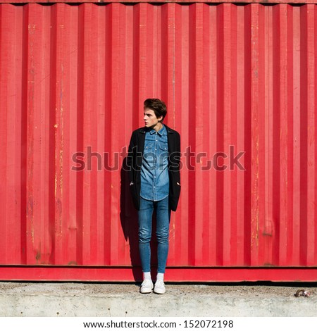 trendy hipster guy in a coat on a red wall - stock photo