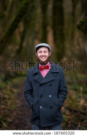 Trendy hipster guy outdoors in the winter in a fashion portrait of the handsome man.