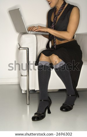 Trendy Hispanic woman typing on laptop against white background.