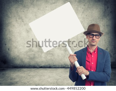 trendy man holding blank protest sign with copy space - stock photo