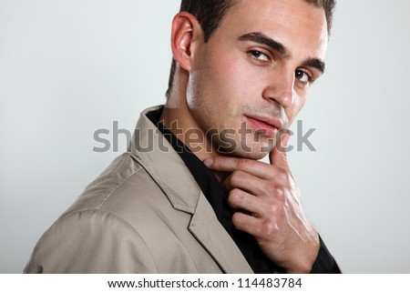 Trendy man in black shirt and beige jacket, portrait of sexy fashion boy looking at camera, isolated