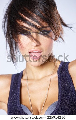 Trendy modern attractive woman with a cute windswept hairstyle looking at the camera with her mouth open  closeup over grey - stock photo