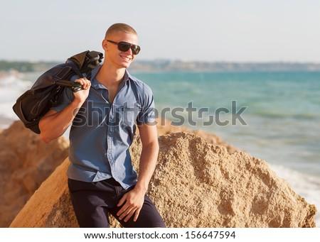 Trendy perfect body guy posing on the beach - stock photo
