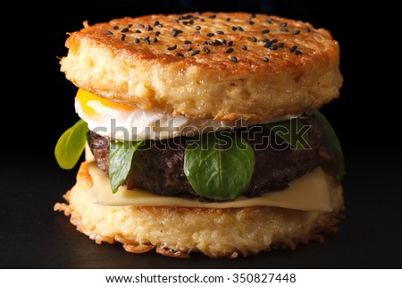 Trendy ramen burger with beef and eggs macro on a black background - stock photo