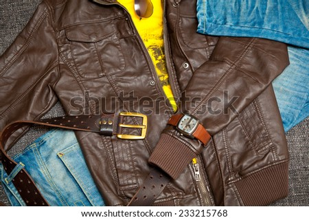 Trendy set for youth. leather jacket, jeans with a belt, shirt, watches and sunglasses - stock photo