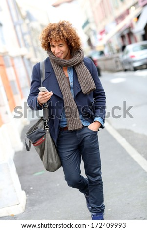 Trendy smiling man talking on phone in the street