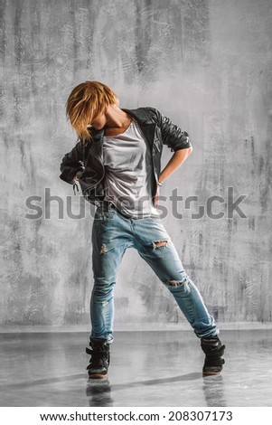 trendy street style dancer jumping on studio background