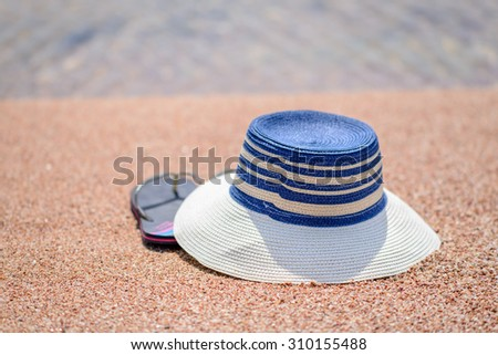 Trendy sunhat and beach thongs or slip slops lying on the golden sand of a tropical beach in the summer sun conceptual of a tropical vacation or getaway - stock photo