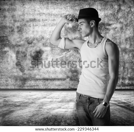 Trendy thoughtful man wearing a fashionable hat and tank top standing in a grunge concrete room staring pensively at the floor - stock photo