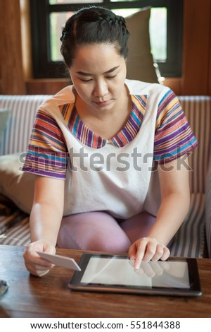 Trendy weekend lifestyle. Woman using tablet pc for online shopping and another hand holding credit card while sitting on a couch. Shopping at home concept.