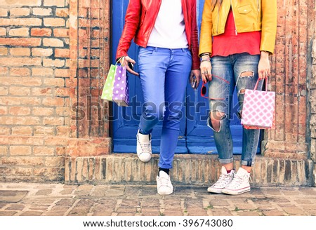 Trendy woman legs and hands holding shoppers next to urban brick wall - Girlfriends with casual colorful clothes and shopping bags in old town - Cropped female legs - Concept of fashion and leisure - stock photo