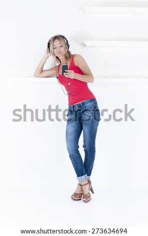 trendy woman listening to music on her mp3 player wearing headphones - stock photo