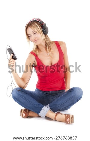 trendy woman listening to music on her mp3 player wearing headphones